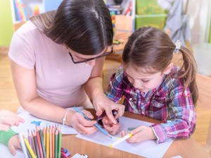 Kindergarten Teacher Supporting Child in Creative Activities